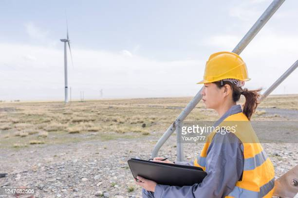 asian female power engineer working at the wind power station - east asia stock pictures, royalty-free photos & images