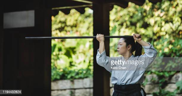 asian female practicing japanese martial art outdoor - martial arts stock pictures, royalty-free photos & images