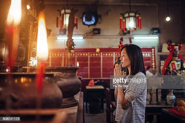 asian female praying sincerely in a chinese temple - religion stockfoto's en -beelden