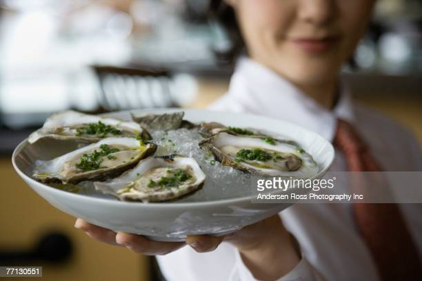 Asian female server holding plate of raw oysters