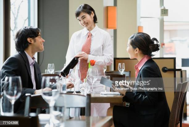 Asian female server showing wine bottle to diners
