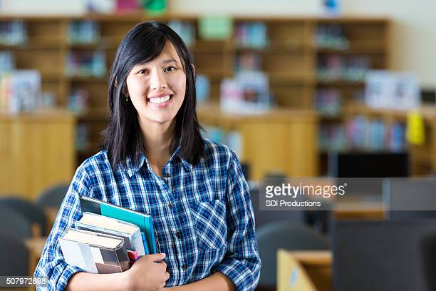 Asian female teacher holding books standing in high school library