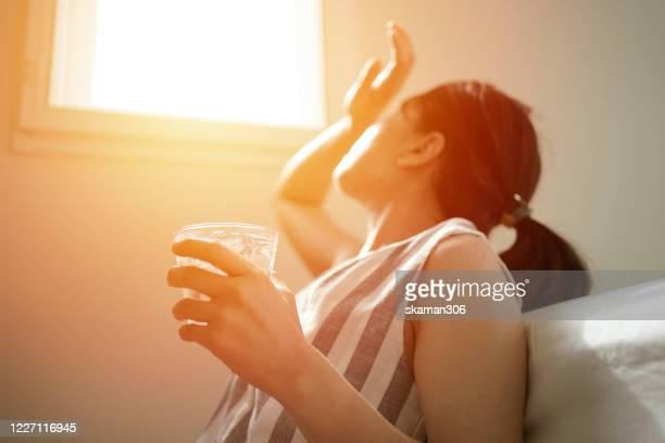 asian female thirsty and dehydration drinking fresh water at summer season at home - medical condition stock pictures, royalty-free photos & images