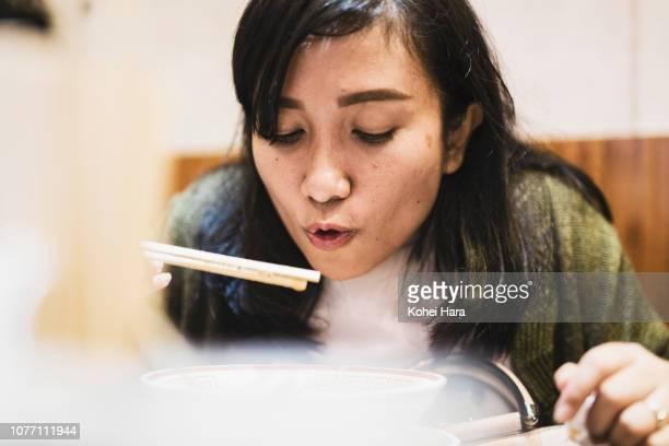 Asian female tourist eating ramen
