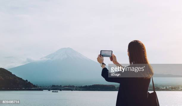 asian female tourist taking pictures of mt fuji with smartphone - capturing an image stock pictures, royalty-free photos & images