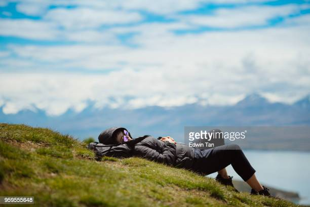 Asian Female Travel Portrait at Lake Tekapo with snow mountain background