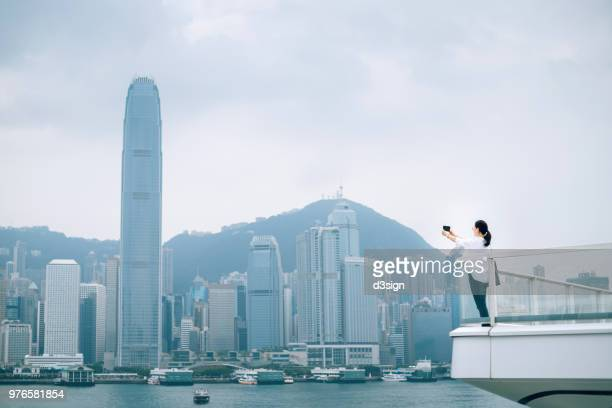 asian female traveller photographing the iconic cityscape with mobile phone from balcony - victoria harbour hong kong stock pictures, royalty-free photos & images