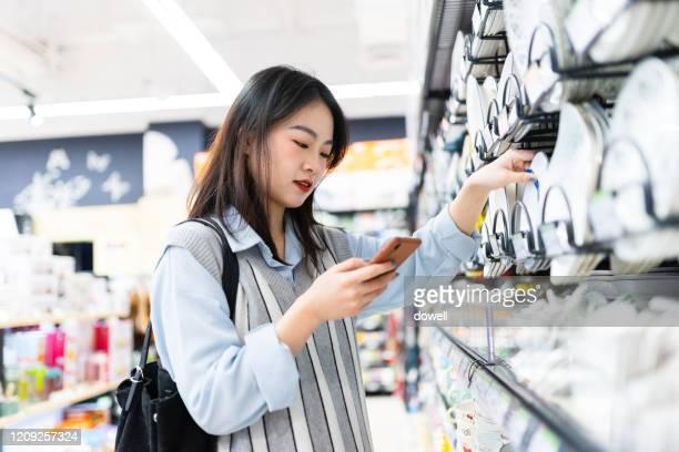 asian female using mobile in supermarket - 台所用品店 ストックフォトと画像