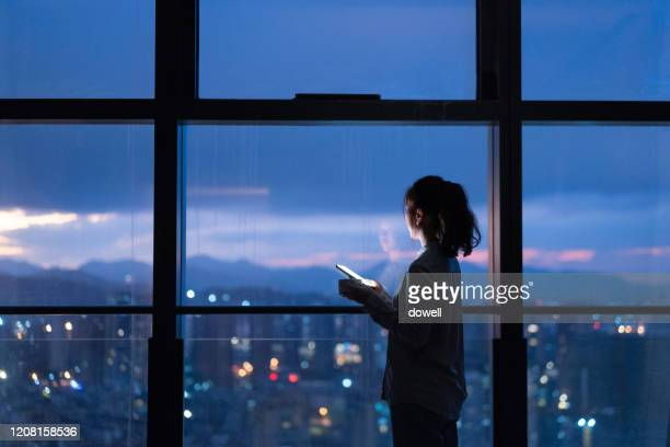 asian female using smart phone at home - individual event stock pictures, royalty-free photos & images