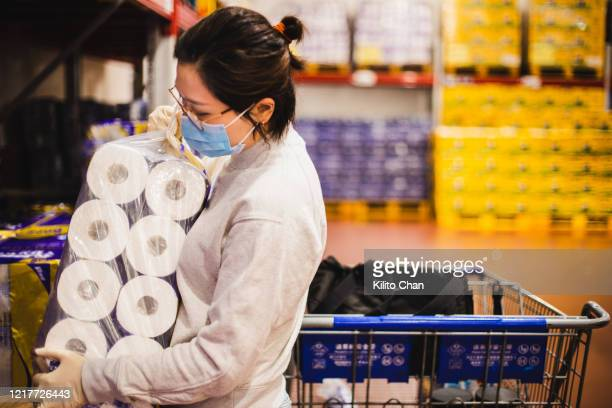 asian female wearing a face mask choosing toilet paper - buying toilet paper stock pictures, royalty-free photos & images