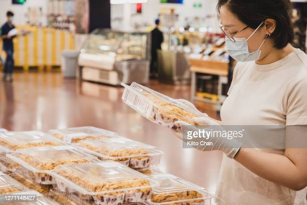 asian female wearing mask buying baked pastry - single use stock pictures, royalty-free photos & images