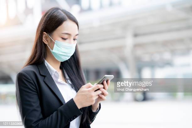 asian female wearing mask protection standing in the business district - south korea stock pictures, royalty-free photos & images