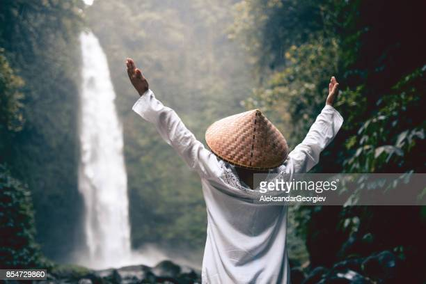 Asian Female with Raised Hands Praying by the Waterfall