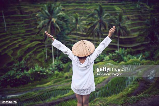 asian female with traditional straw and raised hands at rice fields - vietnam imagens e fotografias de stock