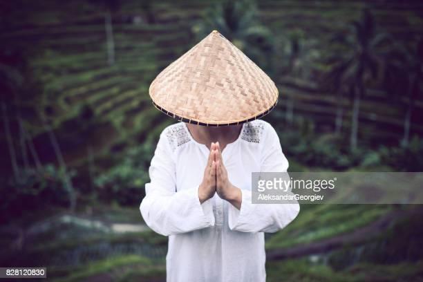 asiatique femme avec de la paille traditionnelle comment prier à champs de riz - chapeau chinois photos et images de collection