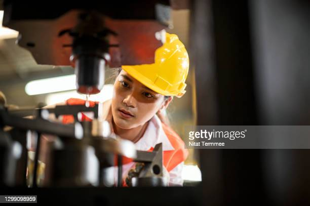 asian female worker control a machine tool in a engineering parts factory. - making stock pictures, royalty-free photos & images