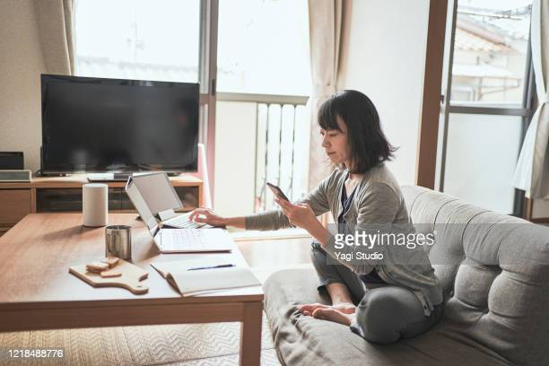 asian female worker working from home. - sólo con adultos fotografías e imágenes de stock