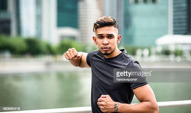 asian fighter man doing a punching boxing training