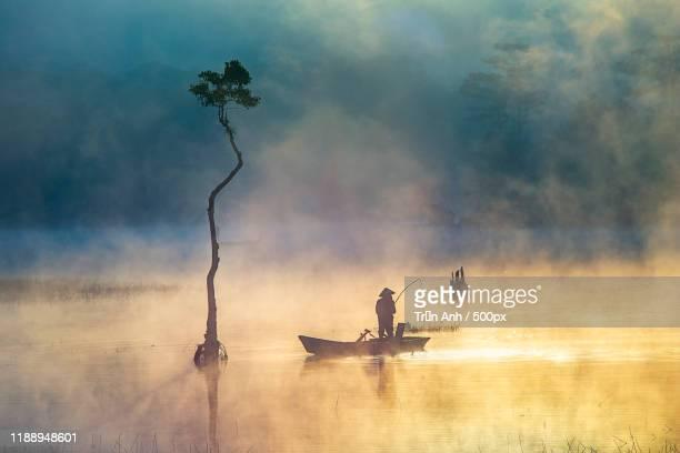asian fisherman in rowboat in lake at sunrise - images stock-fotos und bilder