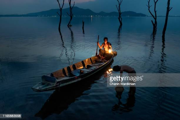 asian fisherman prepare a net for catching a fish in river - tradition stock pictures, royalty-free photos & images