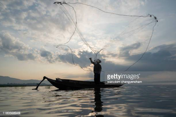 asian fishermen are casting a net their boats on the river. - isla de antigua fotografías e imágenes de stock