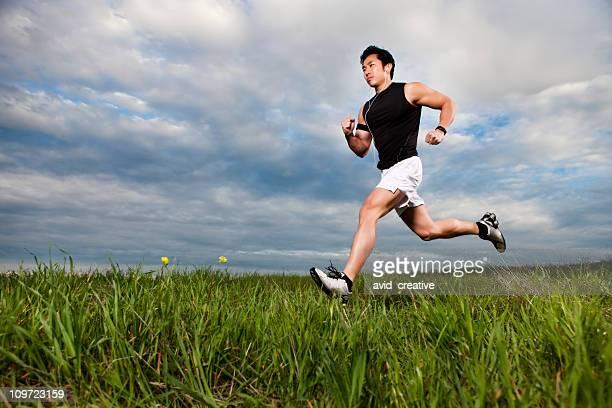 Asian Fitness Man Running Through Field