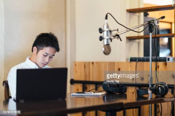 アジアのフリーランス ビデオブロガー、ブロガー、ラジオ dj、ミュージシャンの彼のオフィスでの作業 - ラジオdj ストックフォトと画像