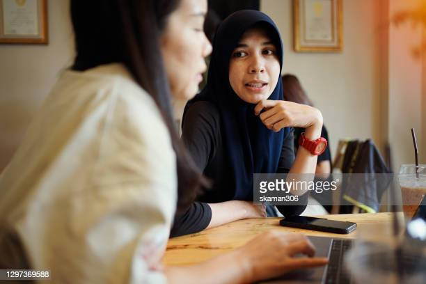 asian freelancer muslim female discuss about work with friend and use laptop computer and cellphone at cafe - thai ethnicity stock pictures, royalty-free photos & images