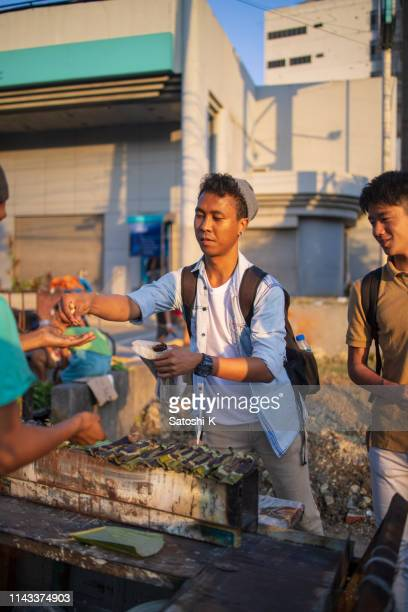 asian friends buying local food at street market - manila philippines stock pictures, royalty-free photos & images