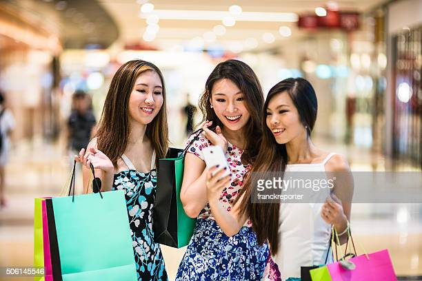 asian friends doing shopping together in singapore - south east asia stock pictures, royalty-free photos & images