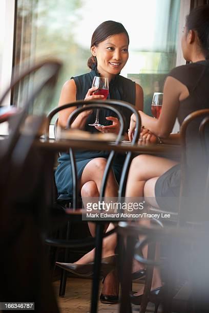 Asian friends drinking wine in cafe