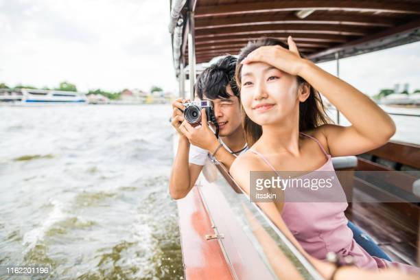 asian friends on the river tour in bangkok next to wat arun - tourboat stock pictures, royalty-free photos & images