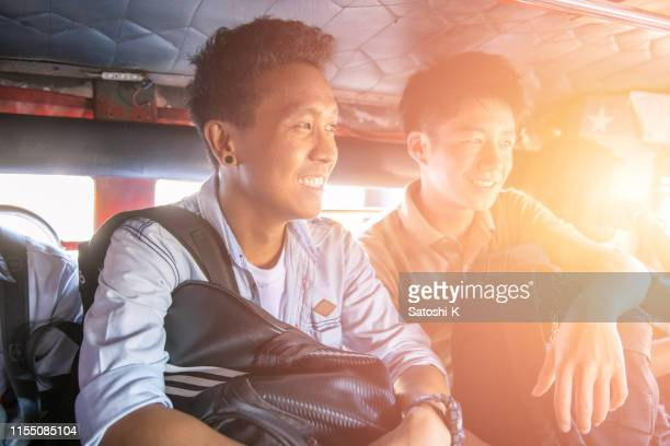 asian friends riding jeepney in manila - jeepney stock pictures, royalty-free photos & images
