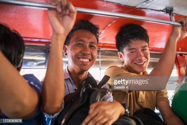 asian friends riding jeepney in philippines - manila philippines stock pictures, royalty-free photos & images