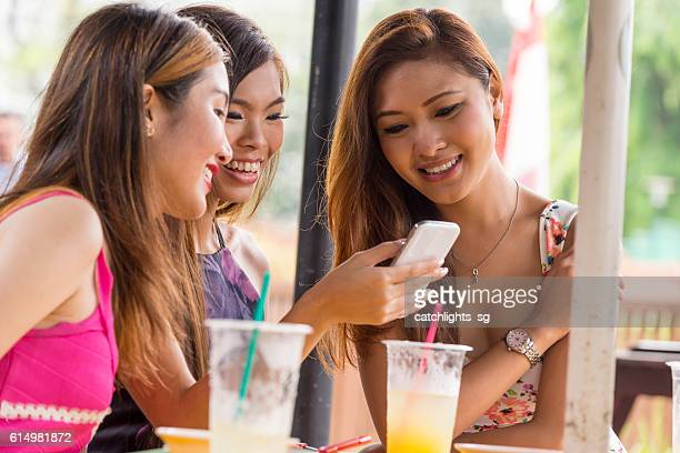 Asian Friends Sharing Photos at Food Court
