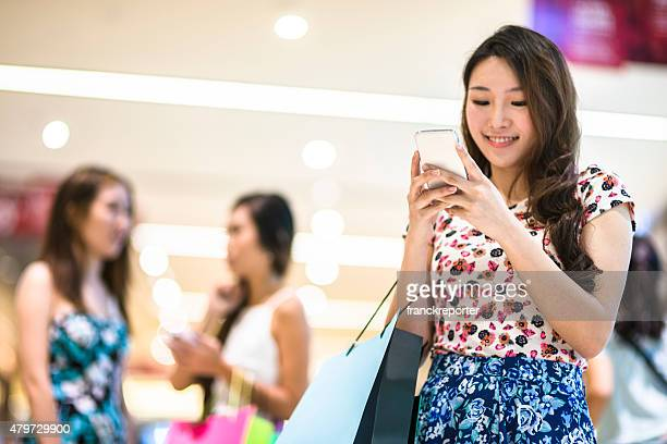 Asian friends text messaging and doing shopping in the mall
