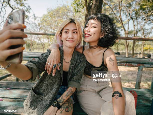 asian friends using smartphone together - social movement stock pictures, royalty-free photos & images
