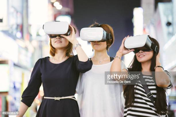 Asian friends using virtual reality simulator outdoors