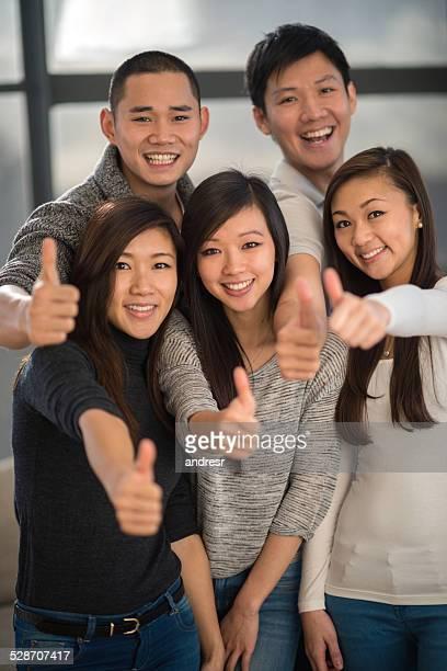 Asiático amigos com polegares para cima