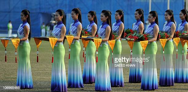 Asian Games hostesses carry medals and bouquets for a medal ceremony of the women's limited overs cricket gold medal final at the 16th Asian Games in...