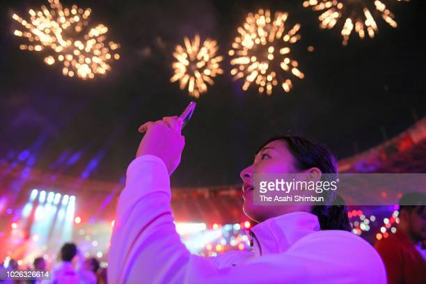 Asian Games MVP Rikako Ikee of Japan takes photographs as fireworks explode during the closing ceremony of the Asian Games at the GBK Main Stadium on...