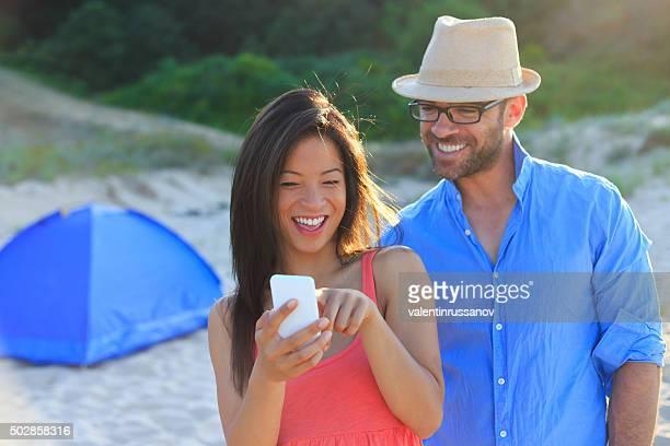 アジアの女性と彼女のボーイフレンドのスマートフォンで写真をお探しですか
