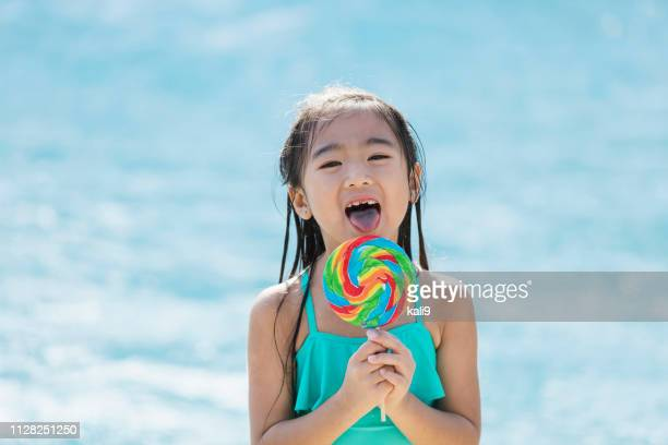 Asian girl at swimming pool with giant lollipop