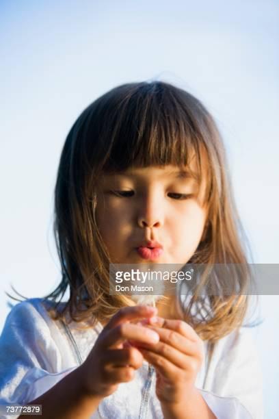 asian girl blowing a dandelion - feuille de pissenlit photos et images de collection