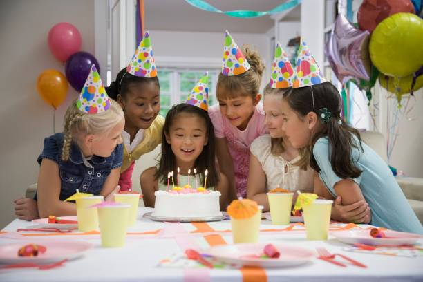 asian girl blowing out candles at birthday party - best friend birthday cake stock pictures, royalty-free photos & images
