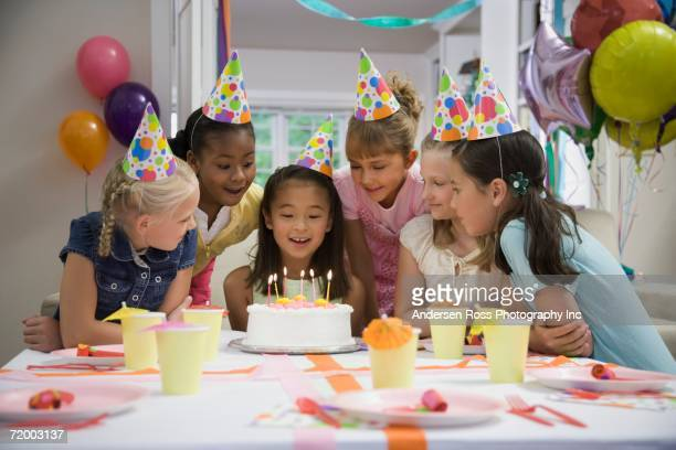 asian girl blowing out candles at birthday party - birthday party stock pictures, royalty-free photos & images