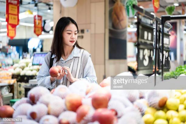 asian girl buy fruit in supermarket - individual event stock pictures, royalty-free photos & images