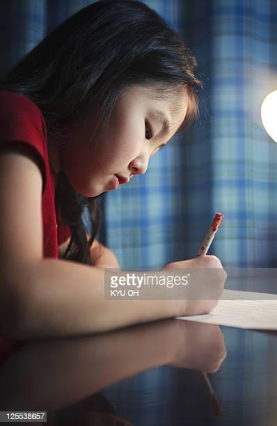 Asian girl doing her homework.
