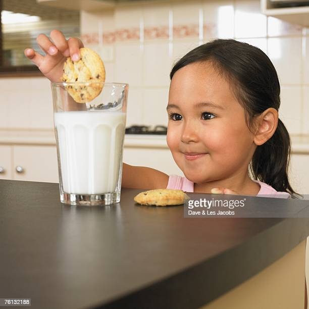 Asian girl dunking cookies in milk