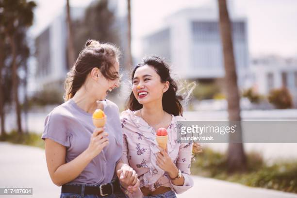 Asian girl eating ice cream and having fun with friend